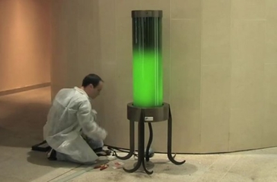 scientist with a glowing green lamp tube